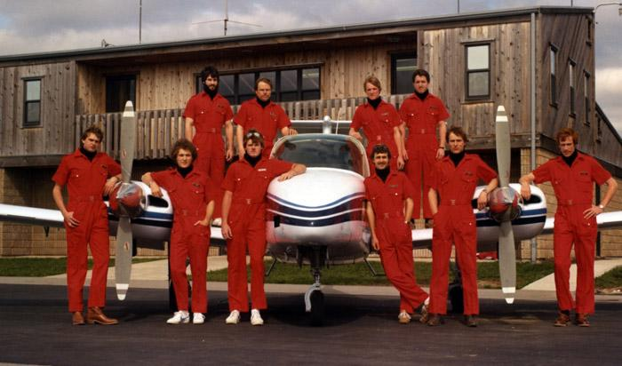 Student pilots in red jumpsuits standing around and on a small airplane.