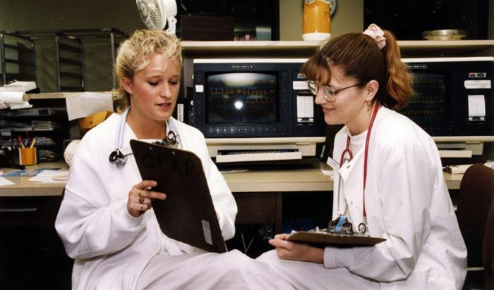 Nursing students looking at a clipboard