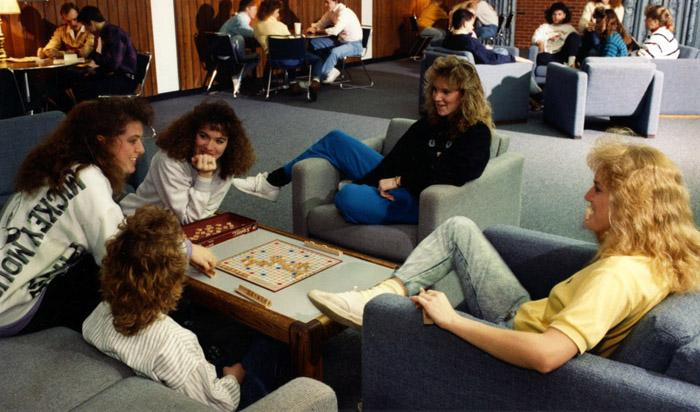 Girls sitting around a table, playing a board game.