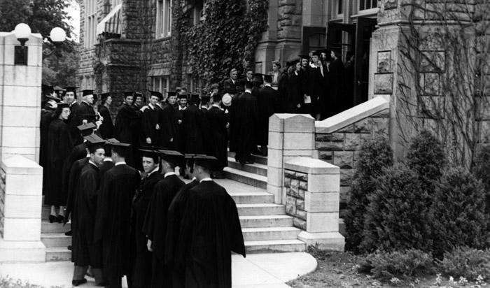 Students standing in line in their caps and gowns waiting to enter Hendricks Hall for graduation.